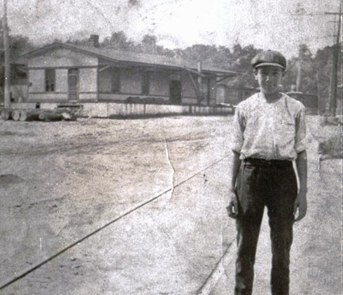 A young man stands with the railroad depot building in the background. This building later became the town post office and barber shop.