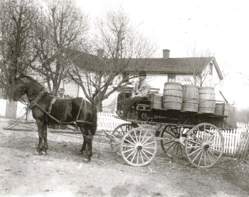 Potatoes in barrels delivered from the Klingenfus family farm (now South Oldham School Campus) via a 20 barrel potato wagon. Oldham County farmers depended on Louisville markets to sell their crops with produce shipped via horse and wagon, and then later via train car.